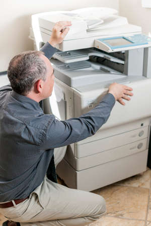 Business man opening photocopy machine in office Stok Fotoğraf