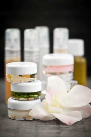 Various jars and bottles of skin care products with orchid flower