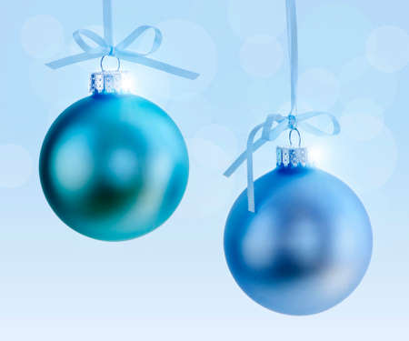 Two Christmas decorations hanging on ribbons with blue background Stock Photo