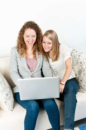 Two young smiling women using laptop computer at home