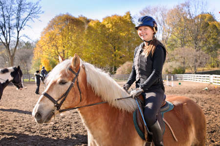 Portrait of teenage girl riding horse outdoors on sunny autumn day 스톡 콘텐츠