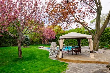Residentiële achtertuin met tuinhuisje, dek, stenen terras en het zwembad