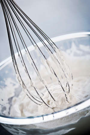 Closeup of metal whisk whipping cream in glass bowl