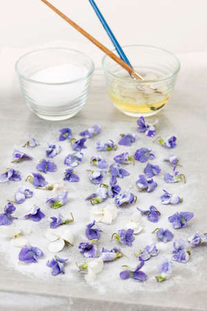 Making candied violet flowers with egg whites and sugar