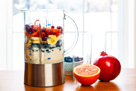 Healthy smoothie ingredients in blender with fresh fruit ready to blend on kitchen table Banco de Imagens