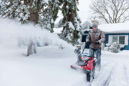 Man using snowblower to clear deep snow on driveway near residential house after heavy snowfall. Zdjęcie Seryjne - 25672664