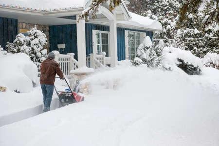 大雪後の住宅の家の近くの私道で深い雪の中をクリアする除雪機を使用している人