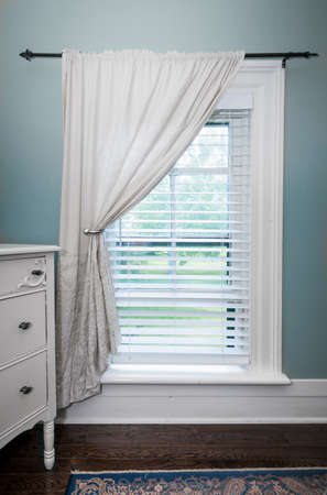 Window with venetian blinds and white curtain in country style room