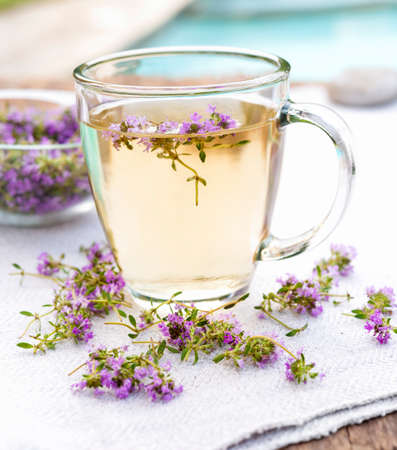 Cup of herbal thyme tea with fresh herb flowers