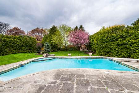 大きなプールと舗装されたテラスで春の住宅の裏庭