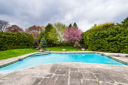 Backyard of residential house in spring with large pool and paved patio