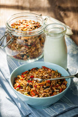 Serving of homemade granola in blue bowl and milk or yogurt on table with linens Фото со стока