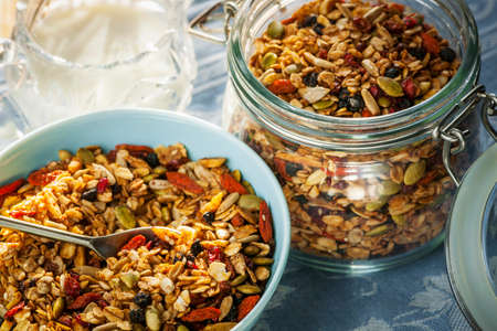 Serving of homemade granola in blue bowl and milk or yogurt on table with linens Foto de archivo