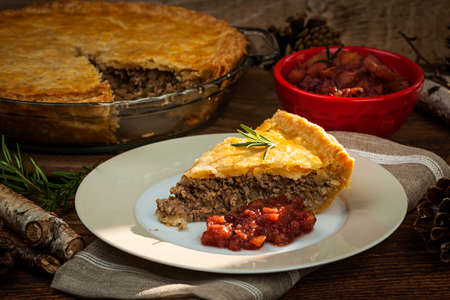 Slice of traditional pork meat pie Tourtiere with apple and cranberry chutney from Quebec, Canada. Stok Fotoğraf - 27340416