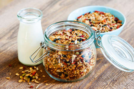 Homemade granola in open glass jar and milk or yogurt  on rustic wooden background