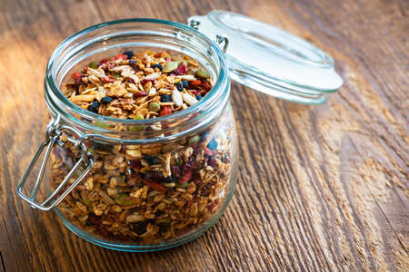 Homemade granola in open glass jar on rustic wooden background Archivio Fotografico