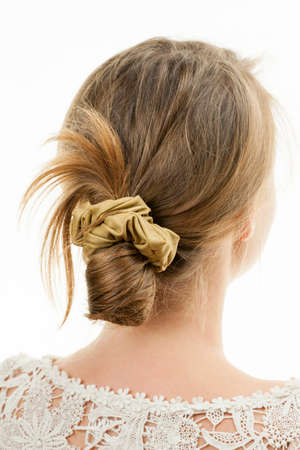 Studio shot of young woman with casual messy chignon hairstyle Foto de archivo