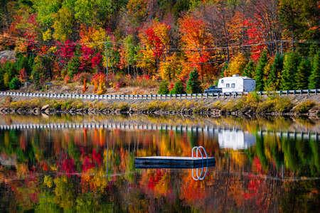 キャンピングカーの運転も紅葉と秋の森は、湖に反映して残します。高速道路の 2 つの川、アルゴンキン州立公園、オンタリオ州、カナダで 60 を。 写真素材