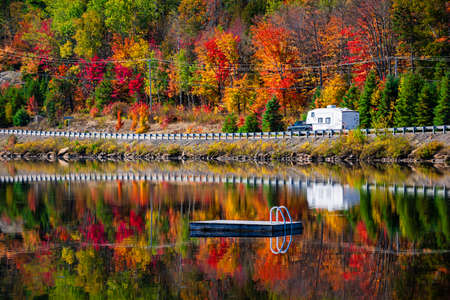 Camper driving though fall forest with colorful autumn leaves reflecting in lake. Highway 60 at Lake of Two Rivers, Algonquin Park, Ontario, Canada. 版權商用圖片 - 28287605