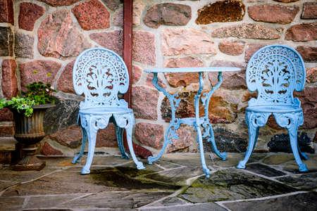 Blue painted metal outdoor furniture on stone patio Standard-Bild