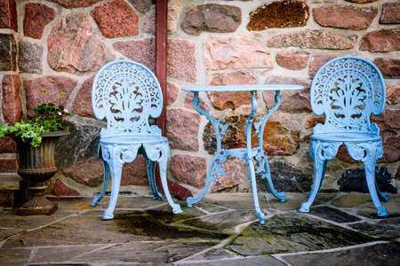 Blue painted metal outdoor furniture on stone patio Stockfoto