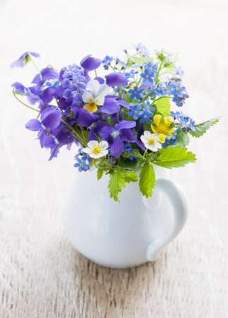 나무 배경에 흰색 꽃병에 야생 꽃의 꽃다발, 스튜디오 촬영