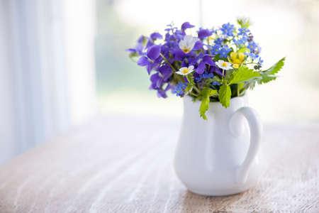 野生の花の素朴な木製のテーブル コピー スペースで、自然光の窓の近くに白い花瓶の花束 写真素材