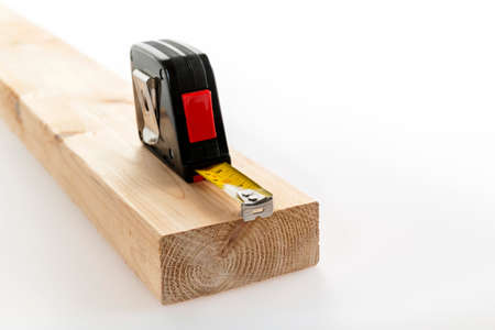 Metal imperial metric tape measure measuring two by four lumber on white background Foto de archivo