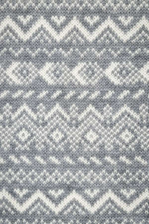 Knit fabric background with knitted grey and white geometric pattern