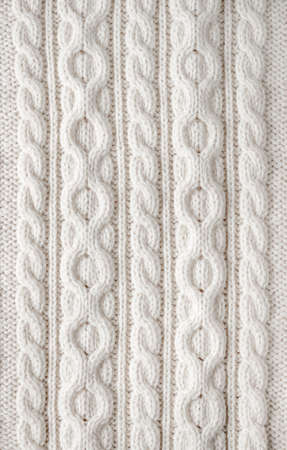 Knit texture of white wool knitted fabric with cable pattern as background