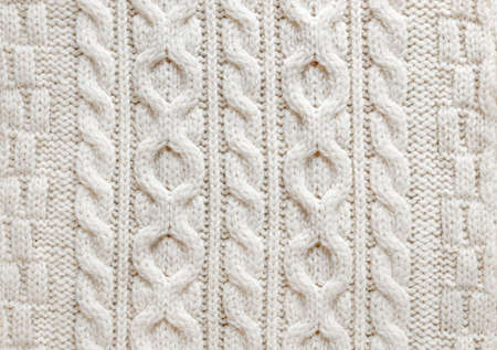 Knit texture of light natural wool knitted fabric with cable pattern as background