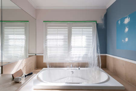 Home renovation of residential bathroom with large tub showing paint roller and sanding block