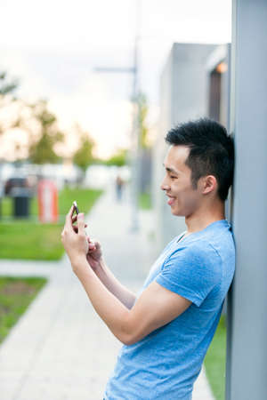 Young asian man smiling and looking at smart phone on city sidewalk