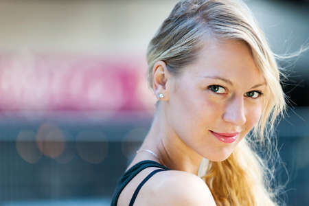 Portrait of young blonde smiling woman looking at camera with copy space