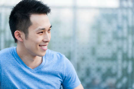 Portrait of confident young asian man in profile smiling on blue background with copy space