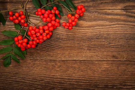 赤いナナカマドや素朴な木製の背景にナナカマドの果実