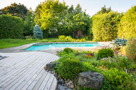 Backyard rock garden with outdoor inground residential swimming pool, curved wooden deck and stone patio Stockfoto
