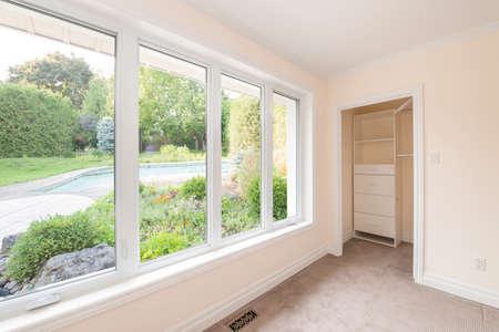 庭園、住宅のプールと夏の裏庭を空の寝室の大きな窓 写真素材