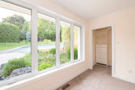 Large window in empty bedroom looking on summer backyard with garden and residential pool Stock Photo - 33879230