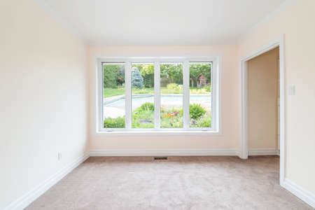 Empty room with large window looking on summer backyard and residential pool