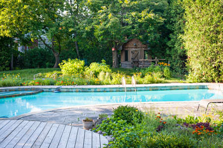 Backyard with garden, shed,  outdoor inground residential swimming pool, curved wooden deck and stone patio