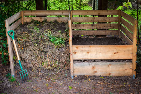 Large cedar wood compost boxes with composted soil and yard waste for backyard composting Stockfoto
