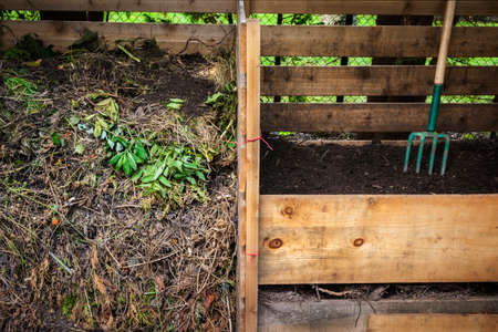 Large cedar wood compost boxes with composted soil and yard waste for backyard composting Foto de archivo