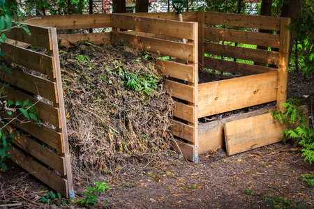 Wooden compost boxes with composted soil and yard waste for garden composting in backyard Foto de archivo
