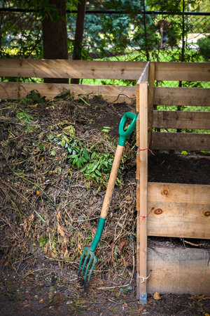 Wooden compost boxes with composted soil and yard waste for backyard garden composting 스톡 콘텐츠