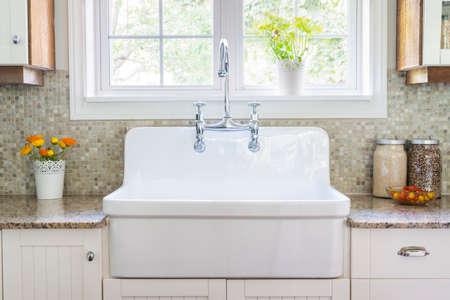 明るい窓の下で大規模な素朴な白い磁器シンクと花崗岩石カウンター キッチン インテリア