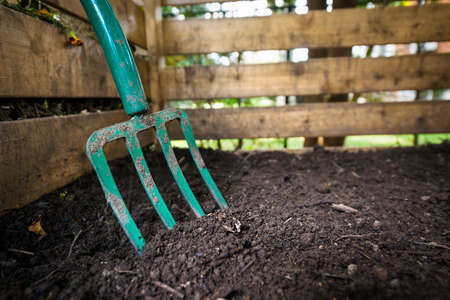 Garden fork turning black composted soil in wooden compost bin Zdjęcie Seryjne - 35906398