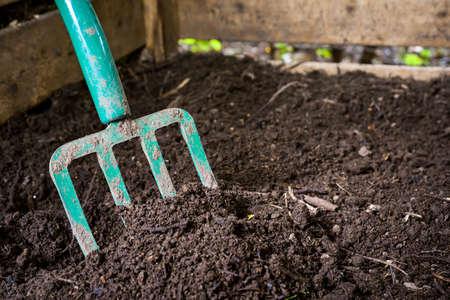 Garden fork turning black composted soil in wooden compost bin