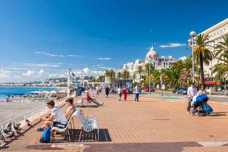 Niza, Francia - 02 de octubre 2014: La gente disfruta de un clima soleado y la vista del mar Mediterráneo en el paseo Inglés (Promenade des Anglais), un gran lugar para caminar, trotar, andar en bicicleta o simplemente relajarse.