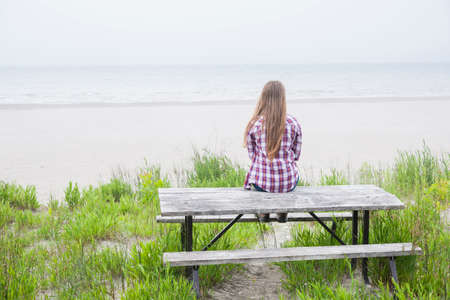 Rear view of young girl with long blond hair sitting on old beach picnic table facing ocean wearing plaid shirt Stock Photo